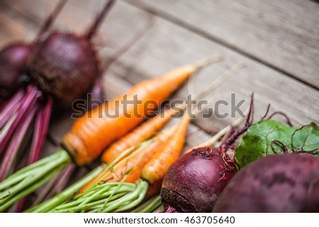 Fresh rustic natural vegetables carrots, beetroots on wooden background. Harvest still life perspective view with selective focus.