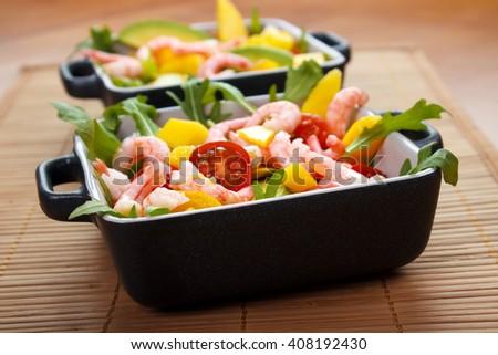 Fresh salad, avocado , shrimps and mango on table matt - stock photo