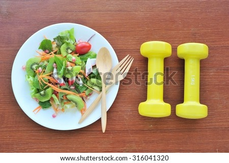 Fresh salad,fruits and greens with dumbbell on wood.Diet concept. - stock photo