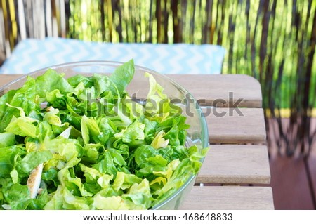 Fresh salad in a glass bowl standing on table