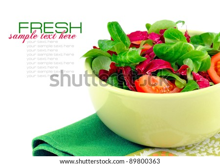Fresh salad is in a dish on a white background