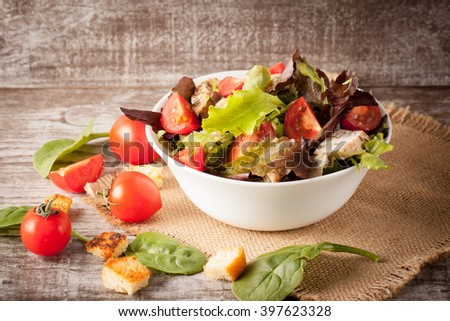 Fresh salad made of tomato, ruccola, chicken breast, arugula, crackers and spices. Caesar salad in a white, transparent bowl on wooden background - stock photo