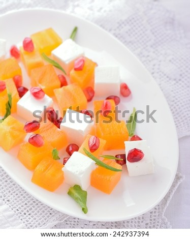 Fresh salad mix with persimmons on wooden table. Selective focus