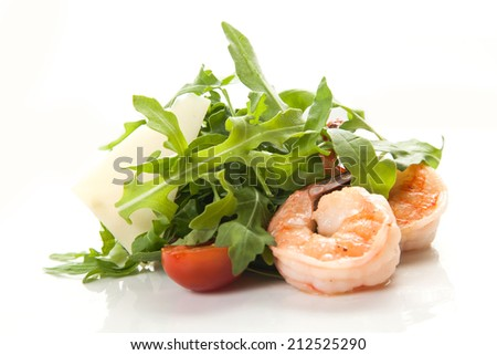 Fresh salad of arugula with king prawns and cherry tomatoes on a white background isolated close-up. - stock photo