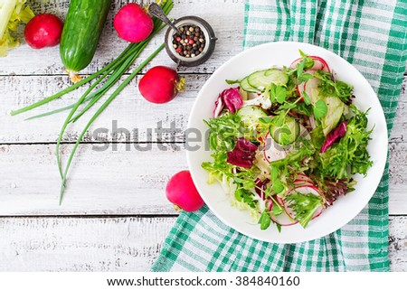 Fresh salad of cucumbers, radishes and herbs. Top view - stock photo