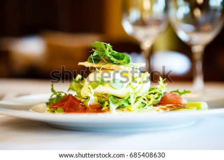Fresh salad of mozzarella, ham and garden asparagus served on white plate