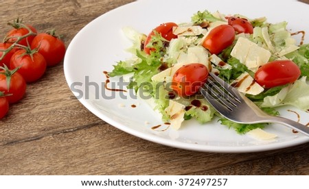 Fresh salad parmesan on a wooden background
