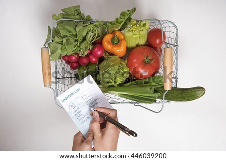FRESH SALAD PRODUCE AND A SHOPPING LIST - JUNE 2016 - UK - A selection of salad crops in a wire shopping basket