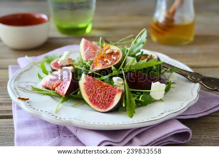 Fresh salad with arugula, figs, slices of cheese and honey, food - stock photo