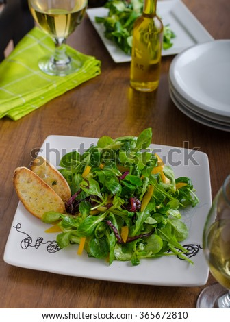 Fresh salad with arugula, lamb lettuce, peppers and caramelized onions. Olive oil baguettes baked to crisp - stock photo