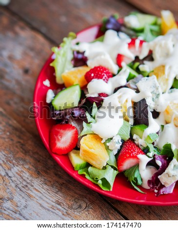 Fresh salad with arugula,spinach,strawberry,orange and blue cheese - stock photo