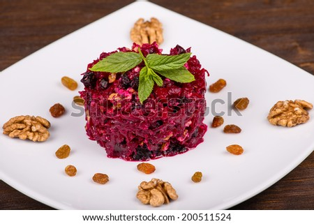 Fresh salad with beet and walnuts on white plate - stock photo