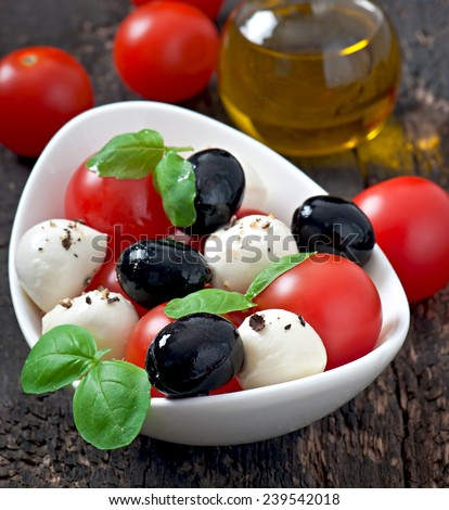 Fresh salad with cherry tomatoes, basil, mozzarella and black olives. - stock photo