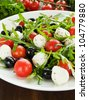 Fresh salad with cherry tomatoes, rucola, mozzarella and black olives. Shallow dof. - stock photo