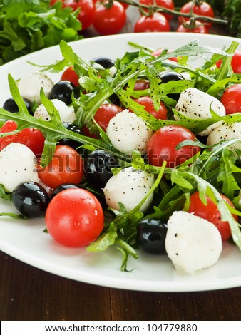 Fresh salad with cherry tomatoes, rucola, mozzarella and black olives. Shallow dof. - stock photo