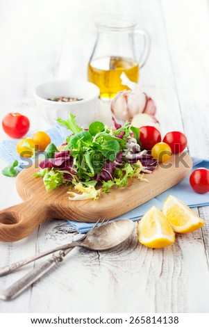 Fresh salad with cherry tomatoes, spinach, arugula, romaine and lettuce on a wooden chopping board on rustic white background, selective focus - stock photo