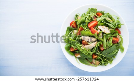Fresh salad with chicken, tomato and greens (spinach, arugula) on blue wooden background top view. Healthy food. Space for text. - stock photo