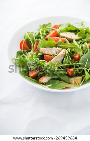 Fresh salad with chicken, tomato and greens (spinach, arugula) on white background close up. Healthy food. - stock photo