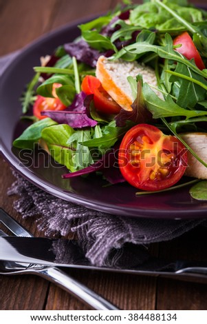 Fresh salad with chicken, tomatoes and mixed greens (arugula, mesclun, mache) on wooden background close up. Healthy food. - stock photo