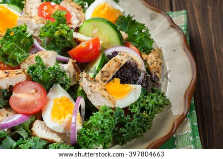 Fresh salad with chicken, tomatoes, eggs and lettuce on plate. Healthy food