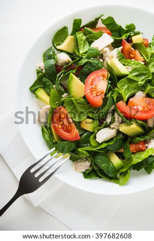 Fresh salad with chicken, tomatoes, spinach and avocado on white wooden background top view. Healthy food. - stock photo