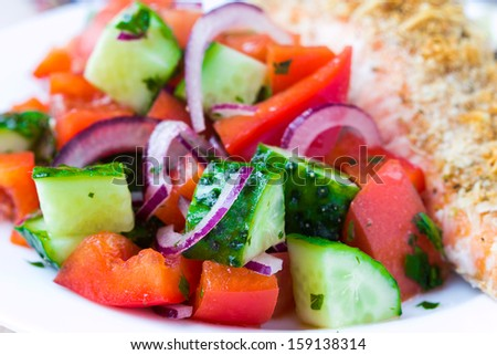 Fresh salad with cucumbers, tomatoes, paprica, onion and fried salmon - stock photo
