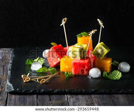 Fresh salad with different kinds of fruits and ice over black background - stock photo