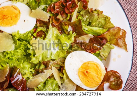Fresh salad with egg and parmesan cheese in a rustic style.