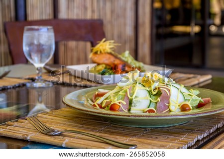 fresh salad with eggs and vegetables served in a small outdoor restaurant, meal time - stock photo