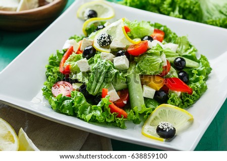 Fresh Salad with feta and olives on white squared plate.