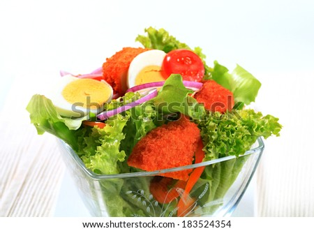 Fresh salad with fried breaded cheese and sliced boiled egg