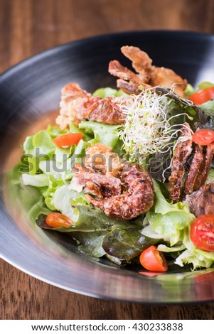Fresh salad with fried shrimps and fried crab on a stainless plate