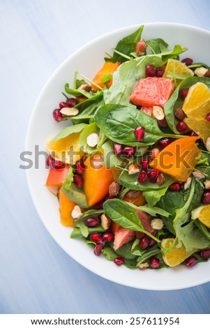 Fresh salad with fruits and greens on blue background top view. Healthy food. - stock photo