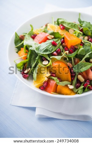 Fresh salad with fruits and greens on blue wooden background close up. Healthy food. - stock photo