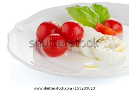 Fresh salad with goat cheese, tomato and basil pesto on a white plate.