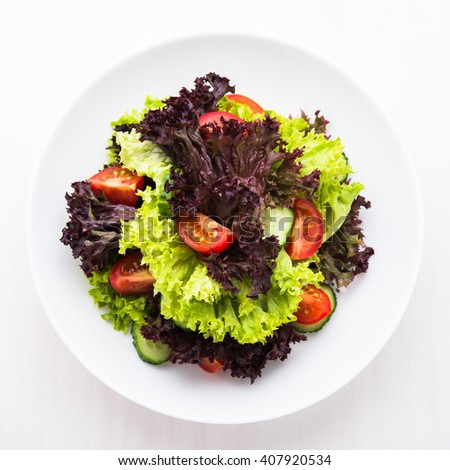 Fresh salad with green and purple lettuce, tomatoes and cucumbers on white wooden background top view. Healthy food. - stock photo