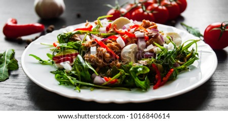 fresh salad with Green rucola, arugula,  cheese, tuna, onion, pepper in white bowl on dark wooden background