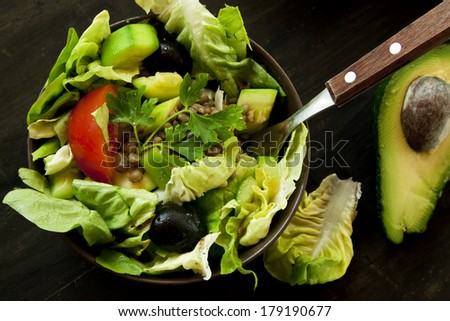 Fresh Salad with Lettuce,Lentils,Olives, Avocado and Parsley, Healthy Green Salad in a Bowl