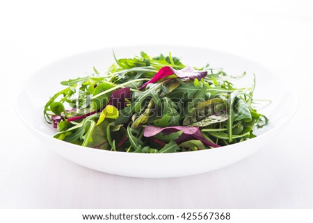 Fresh salad with mixed greens (arugula, mesclun, mache) on white wooden background close up. Healthy food. - stock photo