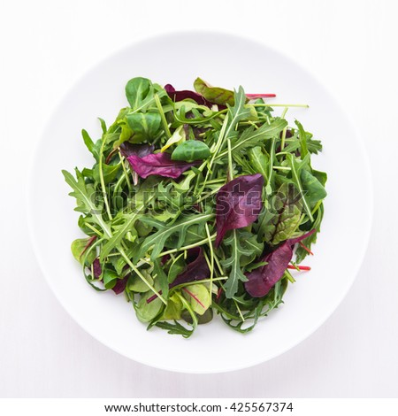 Fresh salad with mixed greens (arugula, mesclun, mache) on white wooden background top view. Healthy food. - stock photo