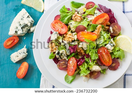 fresh salad with nut grapes and blue cheese on white plate - stock photo