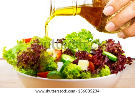 Fresh salad with olive oil isolated on white background, pouring salad dressing into cutting vegetables, organic food, healthy nutrition concept - stock photo