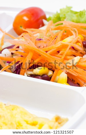 Fresh salad with omelette in white plastic box.