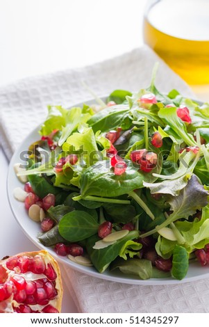 Fresh salad with pomegranate and almonds, extra virgin olive oil.
