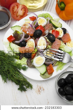 Fresh salad with salmon fillet, on napkin, on a wooden background