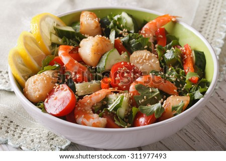Fresh salad with seafood and vegetables in a bowl close-up on the table. horizontal