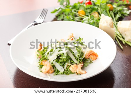 Fresh salad with shrimp and parmesan on wooden table - stock photo