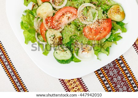 Fresh salad with sliced tomato, cucumber, onion, lettuce seasoned with soy sauce, dry spices and sesame. Top view - stock photo