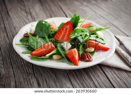 Fresh salad with strawberries, spinach leaves and feta cheese on old wooden background, selective focus - stock photo