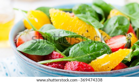 Fresh salad with strawberry, orange and spinach in a bowl on wooden background. Copy space